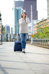 Travel woman walking with suitcase and mobile phone