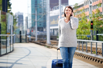 Smiling travel woman talking on mobile phone