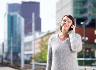 Smiling woman standing in the city with mobile phone