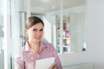 Portrait of a smiling thirty years old woman with her hair tied and wearing a pink shirt. She is holding folders and note books, standing in the hallway of a white office, next to a glass door.