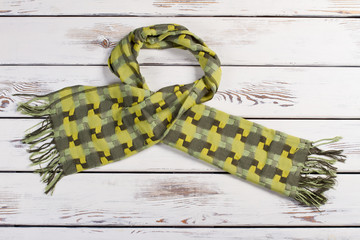 Beautiful green scarf on a wooden background.