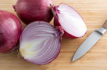 Large red onions on cutting board with knife