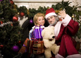 portrait of funny Santa Claus at home with christmass tree, real