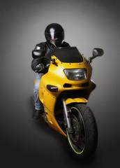 motorcyclist in helmet on yellow motorcycle