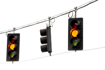 Yellow traffic lights hanging from wires overhead. Isolated against white