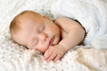 Sweet Newborn Infant Girl Sleeping in White Blankets
