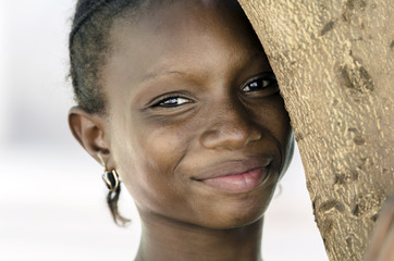 Fashion Portrait of African Teenage Girl Posing and Smiling. Gorgeous African girl posing in the streets of Bamako, Mali. Light smile on her face, standing next to a tree.