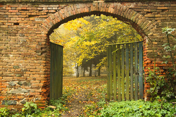 old brick gate opened to the autumn misty park