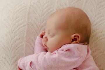 Neugeborenes Baby schläft auf der Seite auf weisser Decke Draufsicht