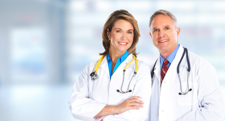 Mature doctors over blue background.