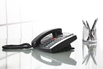 Landliine black phone on an office desk.