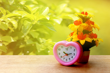 pink clock and flower vase with blur duranta repens background