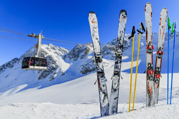 Wall Mural - Skiing, winter season - mountains, cable car and ski equipments on ski run