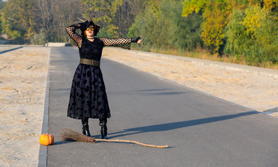Halloween Theme Dressed Lady Hitchhiking on Paved Road Witch in Black Dress Hat and High Heels Boots Run Out of Fuel for Her Broom and Trying to Catch Up Another Mode of Transportation