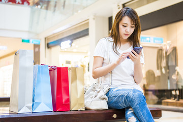 Happy Women holding shopping bags and watching Phone