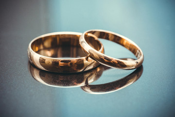 Golden wedding rings isolated on blue background