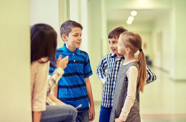 group of smiling school kids talking in corridor