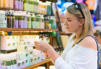 Young woman choosing cosmetic cream in beauty shop.