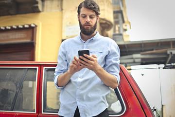 Handsome man sending a text message