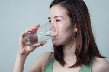 Portrait of Asian women in a green shirt are drinking water from