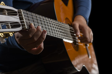 Close-up of child playing classical guitar.