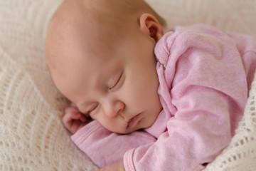 Nahaufnahme neugeborenes Baby schläft zufrieden auf weißer Decke
