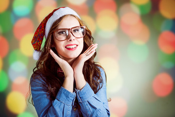 Funny hipster girl in super size eyeglasses wearing xmas hat
