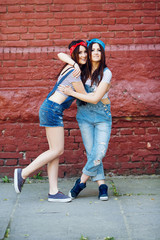 brunette twins girls hugging on brick wall background