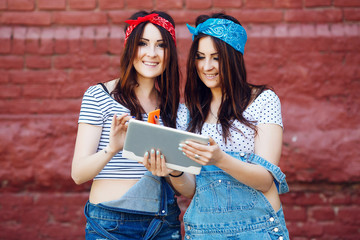 brunette twins girls with tablet and smart phone on brick wall
