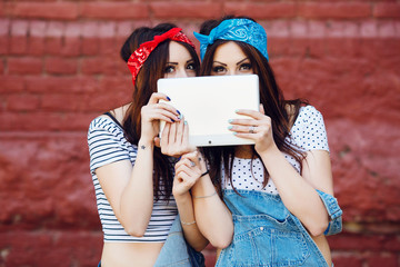brunette twins girls hiding behind tablet