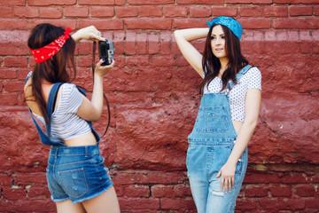 twins girl taking photo on brick wall