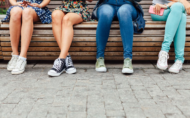 Four teenage girls hanging out on the bench
