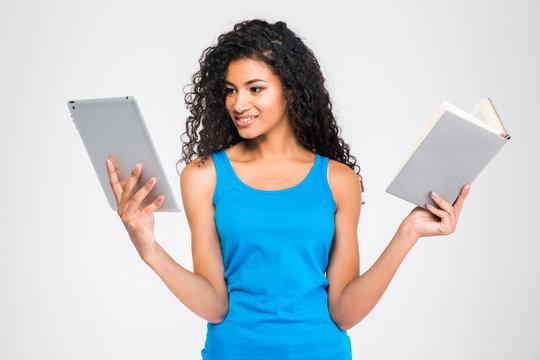 Afro american woman choosing between tablet computer or paper book