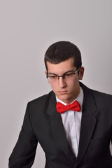 Portrait of an elegant young fashion man in black tuxedo posing