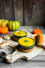 Creamy pumpkin soup with seeds on wooden background