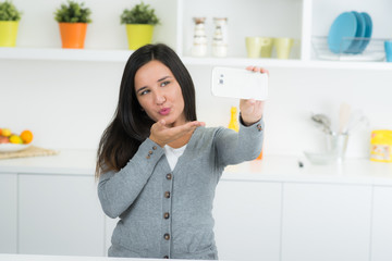 Frau mit Smartphoe in Küche