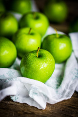 Bright green apples on wooden background