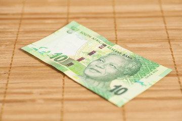 Ten South African Rand on wooden background