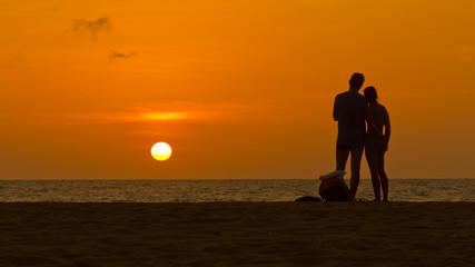 Loving couple enjoying sunset on a sandy beach