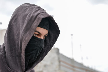 unrecognizable young man wearing black balaclava sitting on old