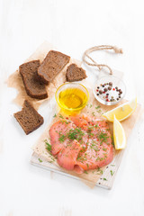 salted salmon, bread and ingredients on a wooden board, vertical
