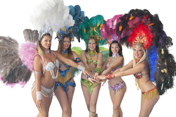 Team of samba dancers joining hands in unity.