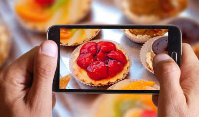 Male hand taking photo of fruit cakes with cell, mobile phone.