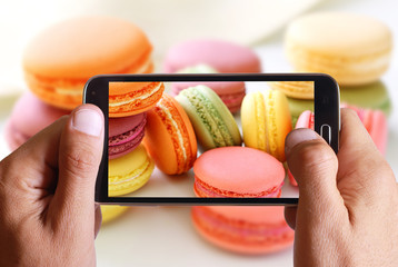 Male hand taking photo of macarons cakes with cell, mobile phone.