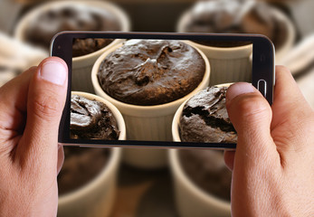 Male hand taking photo of chocolate souffle with cell, mobile phone.