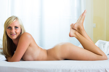 blonde woman with seductive pose in bed