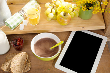 breakfast with milk, bread, tablet and phone, on the edge of a w
