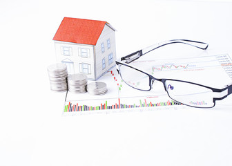 Mortgage loans concept with paper house and coins stack with eyeglasses on financial report