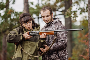 Instructor with woman hunter aiming rifle at firing nature