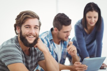 Portrait of smiling man with coworkers using digital tablet